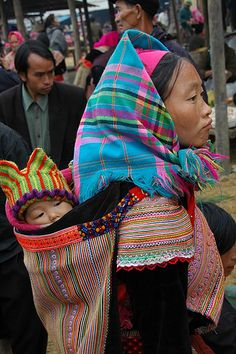 Asia | Portrait of a Hmong mother woman wearing traditional clothes and headscarf carrying her child, Bac Ha market, Vietnam #babywearing