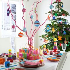 'Children's party' table... lines of thick ribbons laid along the table as an alternative runner.... ribbon-wrapped vase displaying a centrepiece of bendy bamboo twigs which have been spray-painted & decorated with felt baubles...