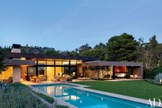 A Beverly Hills home designed by Marmol Radziner is tucked into a hillside to maximize space for the terraces, lawn, and glass-tiled pool, and is marked by deep roof overhangs that provide shade and extend the architecture into the outdoors. Pool House Designs, Modern House Design, Modern Pool House, California Architecture, Modern Architecture, Sustainable Architecture, Residential Architecture, Style At Home, Architectural Digest