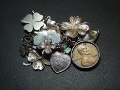 Cluster of sterling silver charms on a sterling silver charm holder. Most are 4 Leaf Clover and good luck charms. One is a lucky penny set in