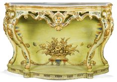 An Italian rococo pale green and polychrome lacquered and parcel-gilt carved console table, Venetian of serpentine form, with an inset beige, grey and white marble top above a pierced frieze on cabriole legs, the solid backboard with a flower and fruit-filled wicker basket above lambrequins on a shaped platform base, the whole carved with scrolls, rocaille and foliage and painted with floral sprays