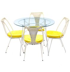 A wrought iron dinette set, having a round table with glass top, on a white iron base with splayed legs on disk feet. The four matching side chairs, feature wrought iron frames with woven nyl. Dinette Sets, Mid Century Modern Furniture, Outdoor Furniture, Outdoor Decor, Wrought Iron, Side Chairs, Seat Cushions, Wicker, Mid-century Modern