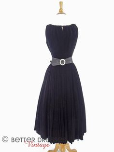 This 1950s party dress is luscious in thick, jet black velvet. Cut to flatter with ballet neckline that's shirred to highlight the bust at front (smooth in back). Narrow center-bodice slit offers a hi