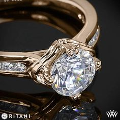 This Diamond Engagement Ring is from the Ritani Modern Collection. The graceful 4 prong head will perfectly house the round diamond center of your choice. The shank holds gorgeous channel-set Round Brilliant Diamond Melee (0.17ctw; G/H VS) and finishes off this look with style. The width tapers from 3.2mm at the top down to 2.1mm at the bottom. Select your diamond from our extensive online diamond inventory. Please allow 12 Business Days for completion. If you have any questions regarding…