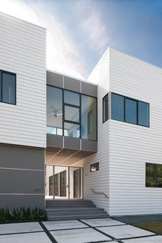 The fiber cement siding, Hardie Plank, is installed flat over vertical screeds, instead of lapped, so we were able to butt the corners together to create a clean corner detail without tri House Cladding, House Siding, Facade House, Courtyard House, Shiplap Siding, Clapboard Siding, White Siding, Exterior Siding Options, Exterior Cladding