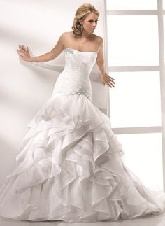 Gown 0251  This beautiful ruffled organza style gown features a stunning full A-line skirt, an extended ruched bodice with beautiful Swarovski crystal embellishments.