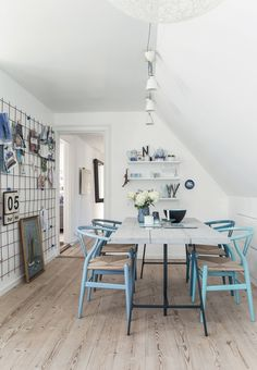 Dining room featuring a rustic plank table with Wegners blue Y-chairs around and a decorative wire wall grid.