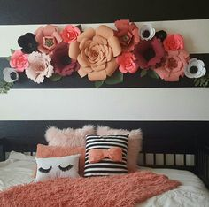 Pink and coral paper flower arch in girls bedroom, black and white striped wall.