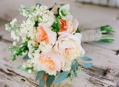 this bouquet is a nice example of more expensive flowers mixed with softer, rustic and less expensive flowers. The white flowers is stock and it also comes in soft pink tones.