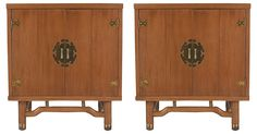 Pair of Asian modernist mahogany cabinets with brass accents. The doors open to reveal one large open space. Oxidation to brass accents.