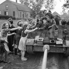 A carrier crew of British 8th Rifle Brigade hands out chocolate to Dutch civilians during the advance of 11th Armoured Division in Holland, 22 September 1944.