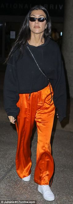 Bright and bold: Kourtney also sported a black sweatshirt, had a chain purse slung across her body, and a pair of white platform sneakers to top off the look