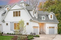 White cottage style house with separate gray garage doors flanked by carriage iron and glass lantern exterior light sconces.