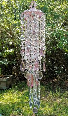 This wind chime is on hold until April 21st. Please do not purchase.  A dazzling pink crystal wind chime!  Antique scalloped brass top is painted a soft cottage chic pink. The piece is surrounded with three layers of beautiful crystal prism and bead strands. There are pink crystal beads, large clear crystal prisms, Swarovski light rose crystal prisms, pink, white and silver beads, pink glass pearls, white opaline crystal beads, pink opaline glass beads, silver metal beads, and pink aurora…