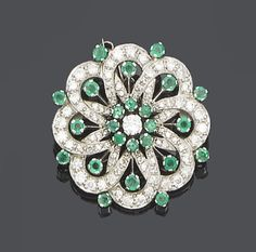 An emerald and diamond brooch  Designed as a flowerhead cluster, the stamen set with a single brilliant-cut diamond, within a border of single-cut diamond openwork petals and circular-cut emerald highlights, diamonds approx. 1.50ct. total, length 3.0cm.