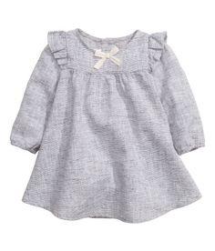 18e - Sieh's dir an! BABY EXCLUSIVE. Kleid aus meliertem Leinen-/Baumwollmischgewebe. Das Kleid hat Volants an den Schultern und vorn eine Zierschleife. Lange Ärmel mit elastischen Abschlüssen. Verschluss im Nacken. – Unter hm.com gibt's noch viel mehr.