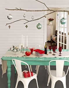 DIY Festive Centerpiece:    Branch out from conventional tablescapes by using an extra-long tree limb as a platform for displaying ornaments. Simply knot lengths of twine around the branch and hang it from a row of five or six ceiling hooks.