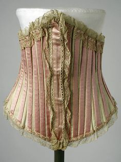 "1900-1905. A plain piece decorated at home? Just speculating of course. The busk cover and lace instantly appear to be add-ons, but when you look at the ""exterior casings"" they're just whipstitched down too. Let's daydream... perhaps a feature added on by a bride for her wedding trousseau?"