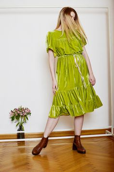 RILEY is a pistachio green silk velvet dress with a loose fit, gathered waist and ruffles at the bottom.