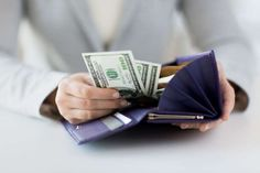 Woman taking out money from wallet - Dolgachov/iStockphoto/Getty Images