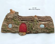 Fairy house made from section of split log lying down, marbles make the windows - I like the way the roof follows the log contours, the knots add character, and the moss sets really well against the bark - the doorstep is a cute touch too (inspiration, sold item, but can be enlarged on site) ***************************************** The Fairy Kingdom #fairy #garden #house