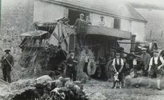 1914 is the year and Lidwell Farm, Dawlish the location. Traction Engine over to the right doing what comes naturally supplying power to the threshing machine belt driven of course.