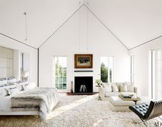 In the master bedroom of entrepreneur Donald Burns's Nantucket, Massachusetts, residence by Jacobsen Architecture, a J. H. Dolph painting hangs above a fireplace with Creel and Gow selenite logs; the bedding by Nancy Stanley Waud Fine Linens is topped with a Dennis Basso fur coverlet, the sofa is by Flexform, and the Mies van der Rohe chair is by Knoll | White, grey, black.