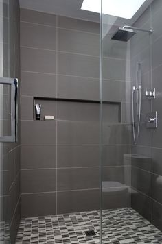 Warm gray porcelain tiles create a modern masculine feel in this recent Woodley Park-DC bathroom remodel. A non-working whirlpool tub was replaced with a generous walk-in shower and frameless glass enclosure. Two seven-foot-high skylights flood the bathroom with natural light and keep the space feeling open and airy.