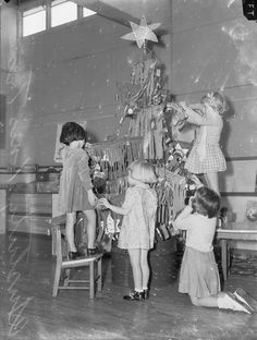 Four little girls decorate their austerity Christmas tree at a suburban Melbourne school. The tree branches are constructed of sticks hung with fringed paper and foil stars are used as decorations.