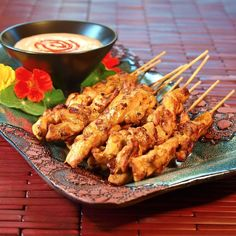 Hot, juicy, succulent, flavorful barbecued chicken on bamboo skewers drizzled with peanut sauce.