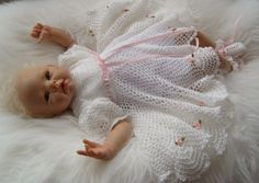 White crochet cotton (2ply (10) with rosebudy trims and pink ribbon, shoes to match.