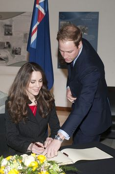 Prince William and Catherine sign the book of condolence in memory of those who lost their lives in the Christchurch earthquake during their visit to the New Zealand High Commission, 25 February 2011.