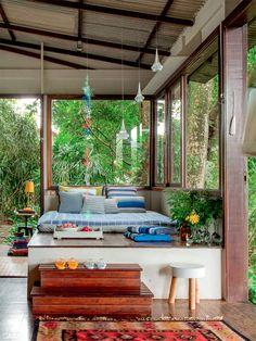Almofadas e colcha (Area Objetos e Gabinete Duilio Sartori) salpicam de cor o futon. O banco faz as vezes de mesa e apoia o abajur (ambos da Area Objetos).