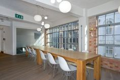 Warehouse-style office space with long meeting table