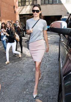 Kendall Jenner wears a gray t-shirt with a pink miniskirt and metallic heels