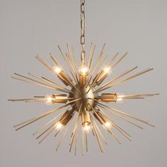 A mid-century modern statement piece, our exclusive chandelier is crafted of iron with a matte brass finish and nine exposed candelabra bulbs. Dozens of rods extend from the central orb like a starburst, glowing radiantly when illuminated and sending warm streams of light into the dining or living room.