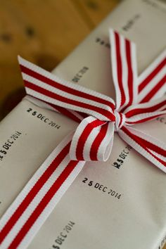 Christmas gift wrapping: date stamp + newsprint + festive ribbon