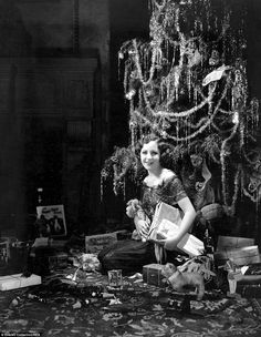 A woman sits at the foot of a tinsel-covered Christmas tree surrounded by string-tied pres...