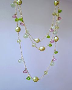 Solid 14k gold opera length chain adorned with fine quality natural gemstones in shades of pink and green and outstanding olive green to golden South Sea pearls. By Maria Cossutta. Made in Monte Carlo. Exquisite luxury (as seen at high end department stores).  82cm long. Best worn as a single layer (although can be doubled).  Sparkling bright green peridot (natural) and mysterious bluish green glowing prehnite (natural). Pink topaz (natural).  South Sea pearls of AA+ quality, some have tiny…