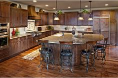 Rustic wood and iron stools surround this fan-shaped island. The Valencia Plan by Celebrity Communities at Pradera. Newly built homes in Parker, CO.