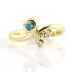 Engagement ring made of 14k gold with an ocean blue and two white diamonds. The ring meanders around the finger like a small, glittering wave. It has been soldered together, but could just as well have been open and thus have trickled further up the finger and down the back of the hand.
