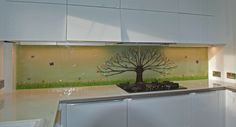 This is a 2.8 m long bespoke splashback in Scotland, featuring a Tree of Life. Our client wanted a soft green background colour, and that contrasts well with the mighty brown tree, resplendent with multicoloured leaves and adorned with olives and birds. This colour scheme is very well suited for a kitchen splashback, as it connotes great cooking and is associated with peace and quiet. That's exactly what the client has in Hamilton, and we're glad that they enjoy their bespoke splashback.