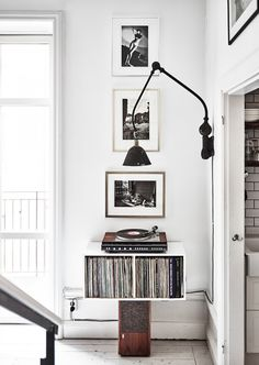Balancing a shelf of records on a speaker with wall art above and a sconce on the side. White walls.