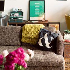 どうしても生活感が出てしまう収納ラックなどはソファの裏側に配置し、できるだけ視界に入らないようにするのもテク。上のウォールにピンナップをレイアウトして視線をそらせるのも手です。