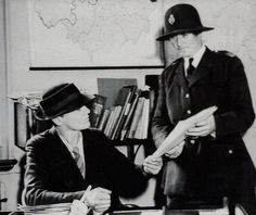 The first Metropolitan Police female Superintendent Dorothy Olivia Georgiana Peto being shown some papers by WPC Sophie Alloway in 1937. Dorothy is the person wearing the trilby and tie.