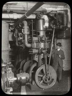 Central building, engine room : man, pipe in hand, standing beside machinery, ca. 1920s. NYPL Archives.