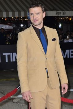 Justin Timberlake sporting a great looking combo of a brown shirt with blue tie and camel colored suit.