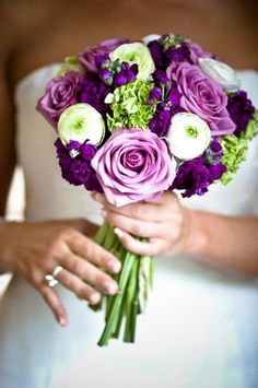 clutch bouquets of green hydrangeas, dark purple lisianthus, lavender spray roses, purple calla lilies, purple stock flowers, and green bupleurum wrapped in purple ribbon with stems showing