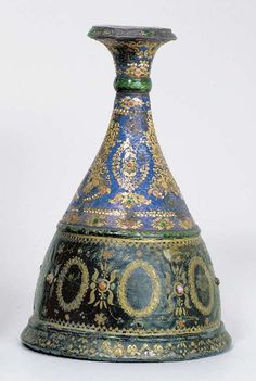 A QAJAR ENAMELLED SILVER NARGILEH BASE  Probably Shiraz, South East Iran, mid 19th century  Of curving conical form with flaring mouth, the copper body painted with wreaths alternating with leafy sprays in gold with applied beads, the neck with very delicately drawn gold floral sprays dividing wreaths inset with glass beads on a cobalt-blue glass ground, bands of similar decoration above and below, the flaring mouth similar, green enamelling on the raised dividing bands,  9 1/8in. high
