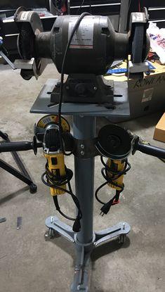 Angle grinder holder attached to bench grinder stand.